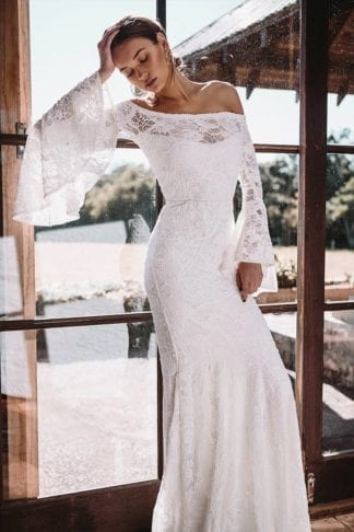 Brunette bride wearing Grace Loves Lace Sloane Gown with hand on hair leaning on glass door