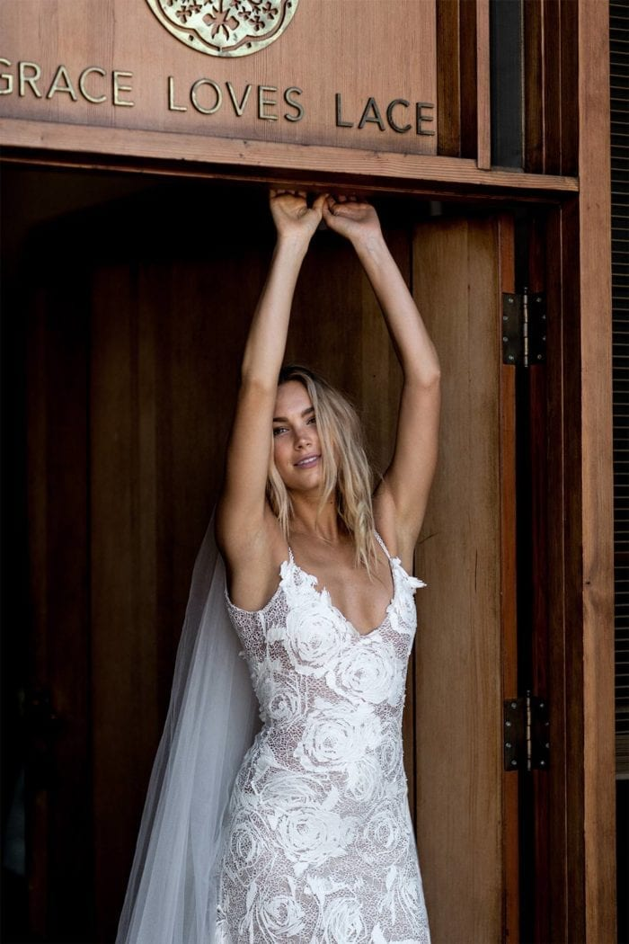 Bride wearing Grace Loves Lace Rosa Gown with hands stretch up on doorway