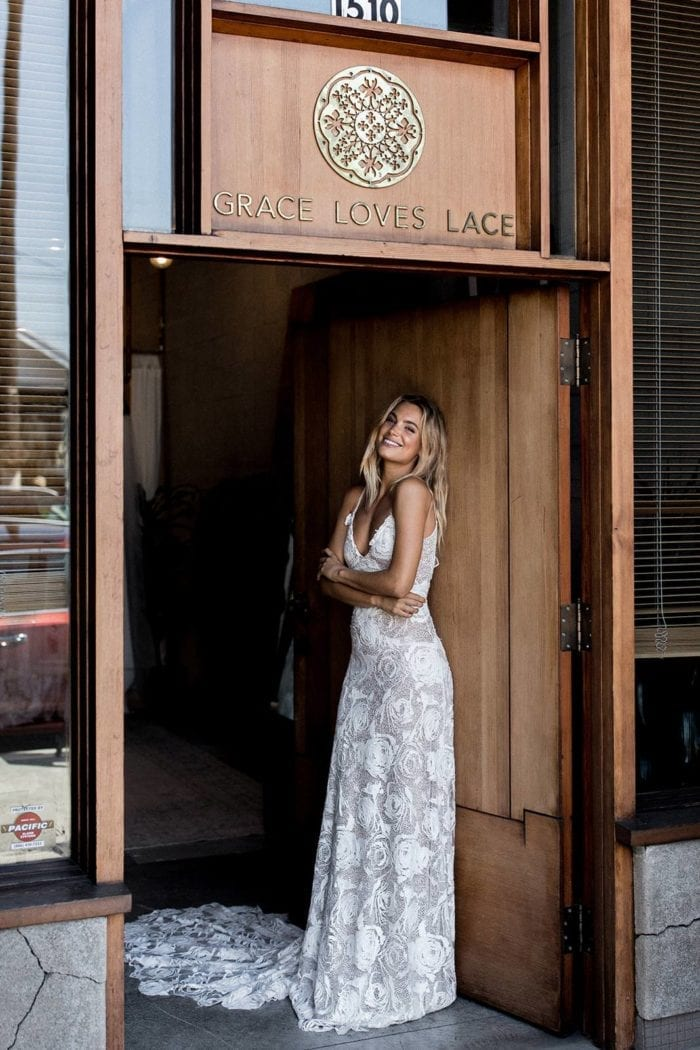 Bride wearing Grace Loves Lace Rosa Gown leaning against door in doorway
