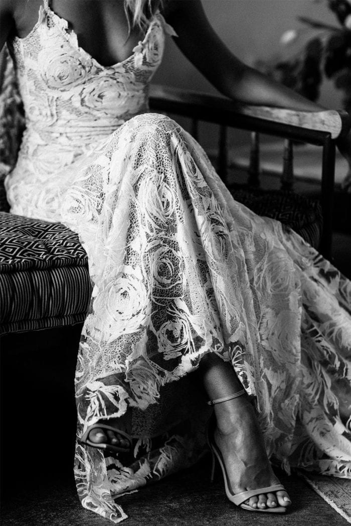 Black and white shot of bride wearing Grace Loves Lace Rosa Down sitting on sofa with legs crossed