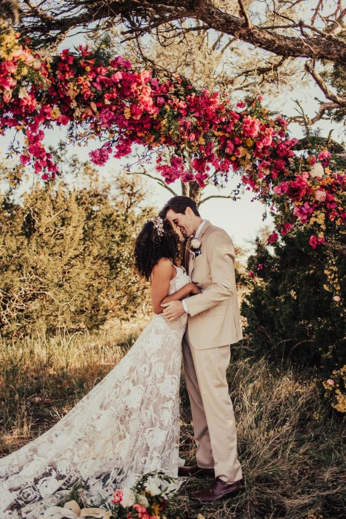 Side shot of bride wearing Grace Loves Lace Rosa Gown kissing groom under pink tree