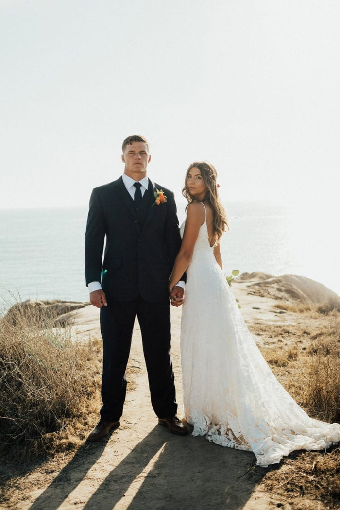 Bride wearing Grace Loves Lace Rosa Gown holding hands with groom