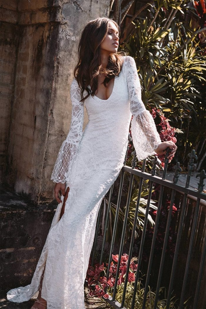 Brunette bride wearing Grace Loves Lace Piper Gown leaning against fence