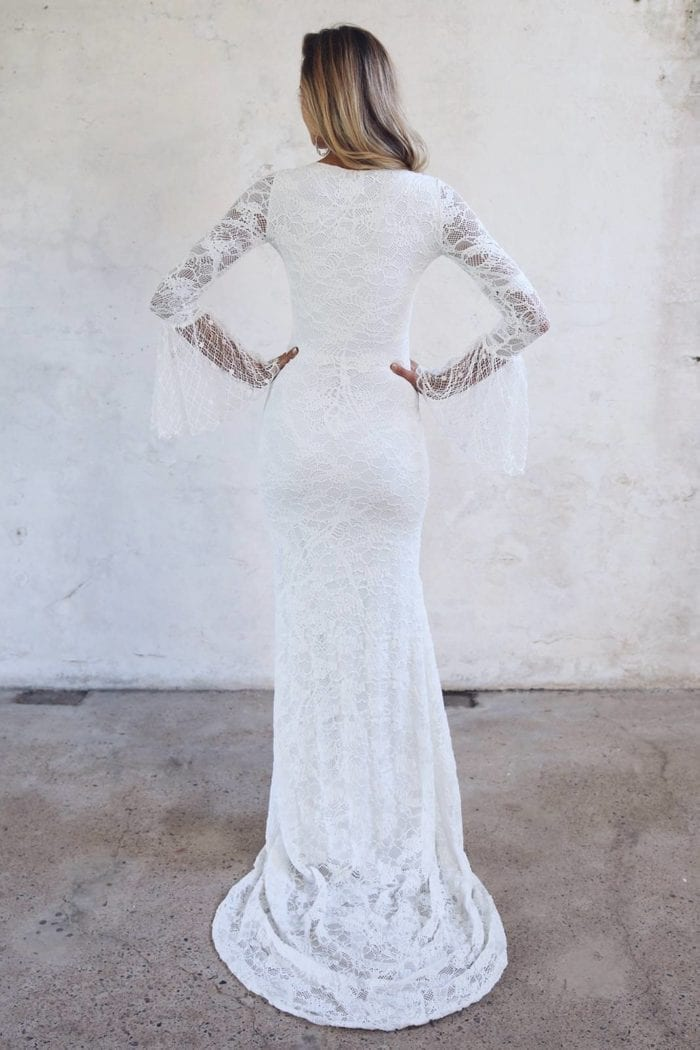 Back shot of blonde bride wearing Grace Loves Lace Piper Gown with hands on hips