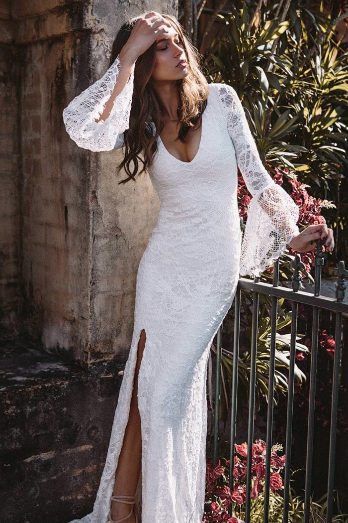 Brunette bride wearing Grace Loves Lace Piper Gown with hand on hair leaning on fence