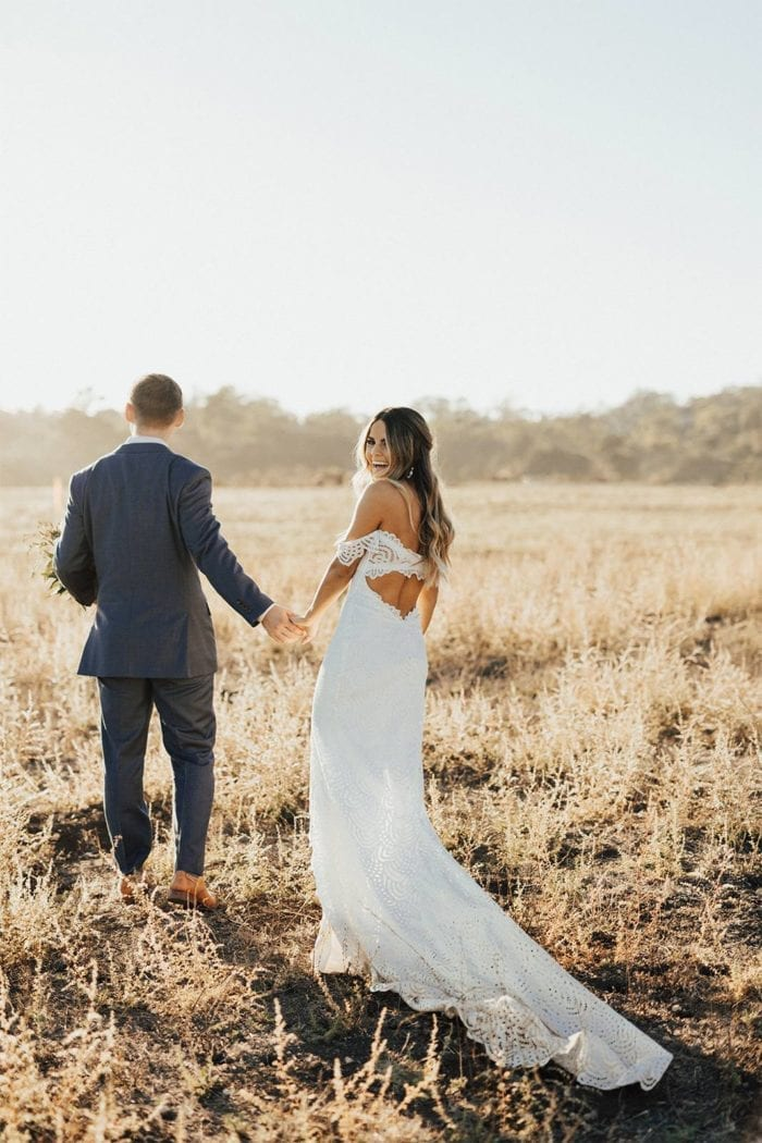 Brunette bride wearing Grace Loves Lace Paloma Gown holding hands with groom