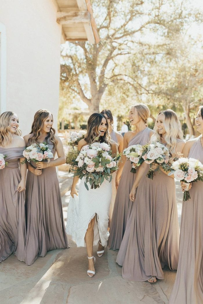 Blonde bride wearing Grace Loves Lace Paloma Gown holding bouquet with bridesmaids