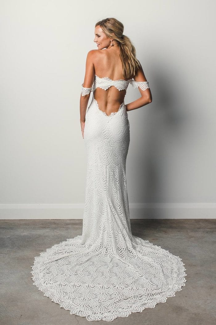 Back shot of bride wearing Grace Loves Lace Paloma Gown holding bouquet