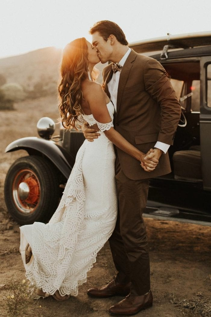 Blonde bride wearing Grace Loves Lace Paloma Gown kissing groom in front of classic car