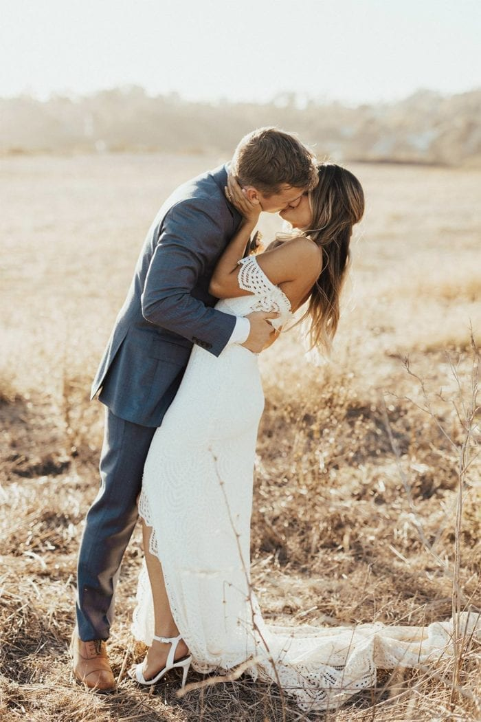 Brunette bride wearing Grace Loves Lace Paloma Gown kissing groom