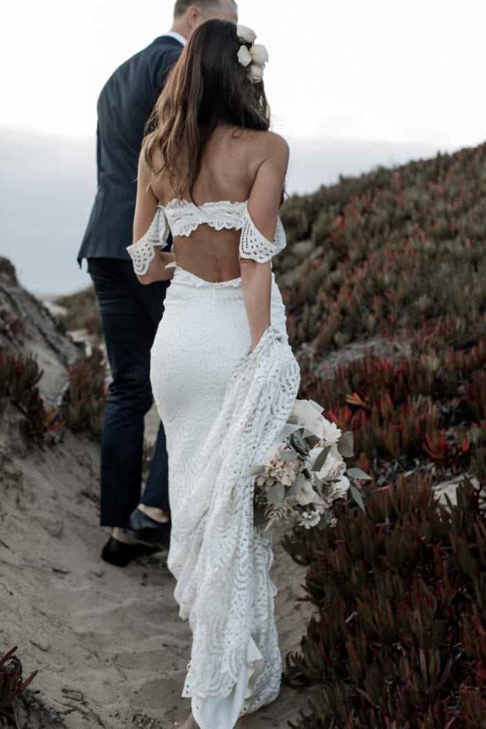 Brunette bride wearing Grace Loves Lace Paloma Gown walking with groom
