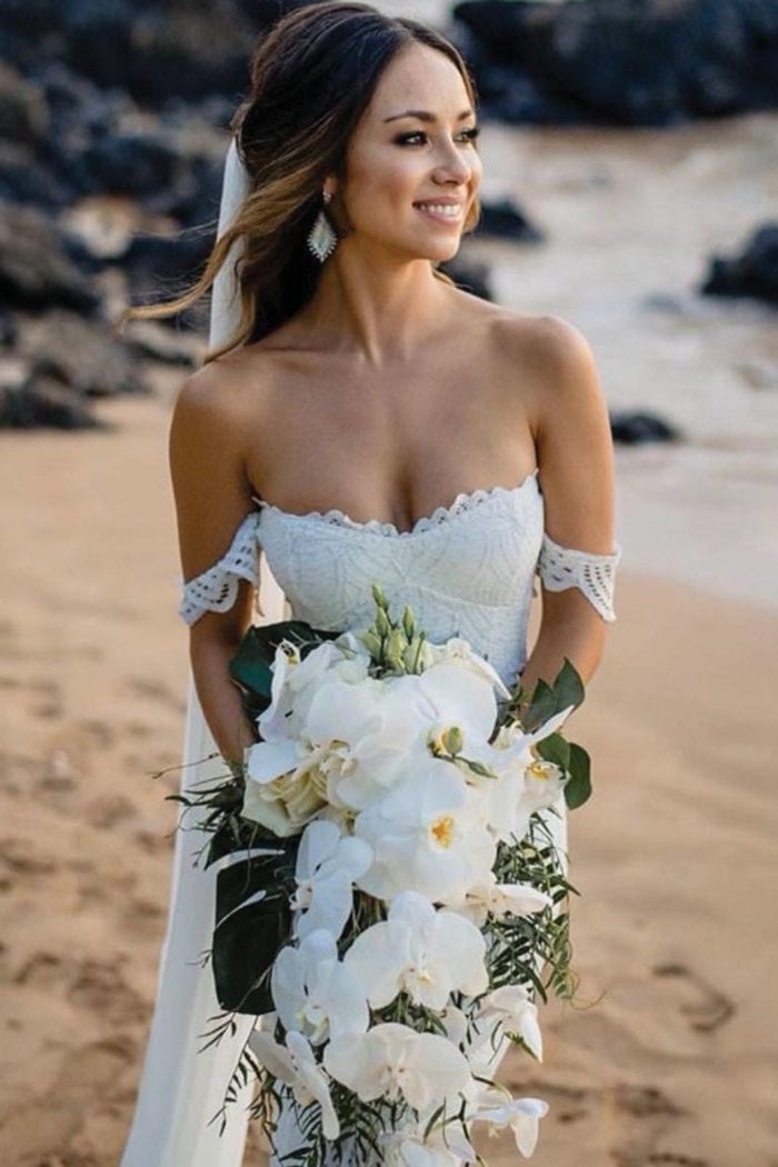 Brunette bride wearing Grace Loves Lace Paloma Gown holding bouquet on beach