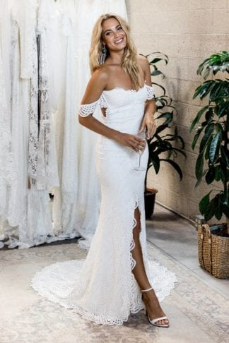 Blonde bride wearing Grace Loves Lace Paloma Gown holding champagne glass