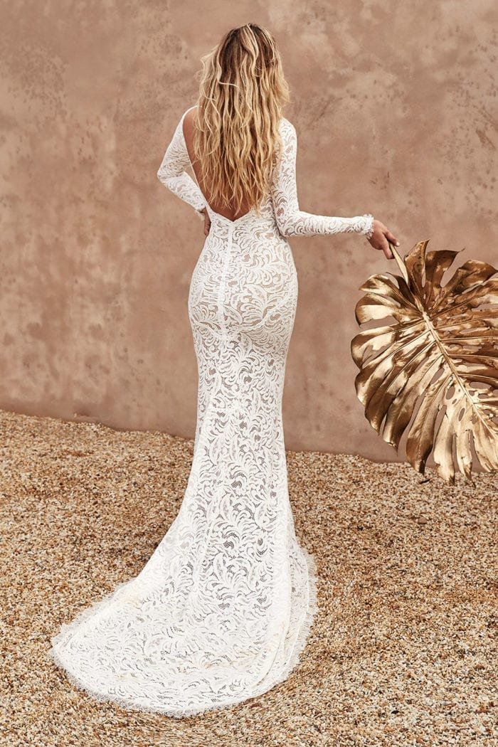 Back shot of bride wearing Grace Loves Lace Orla Gown holding gold palm frond