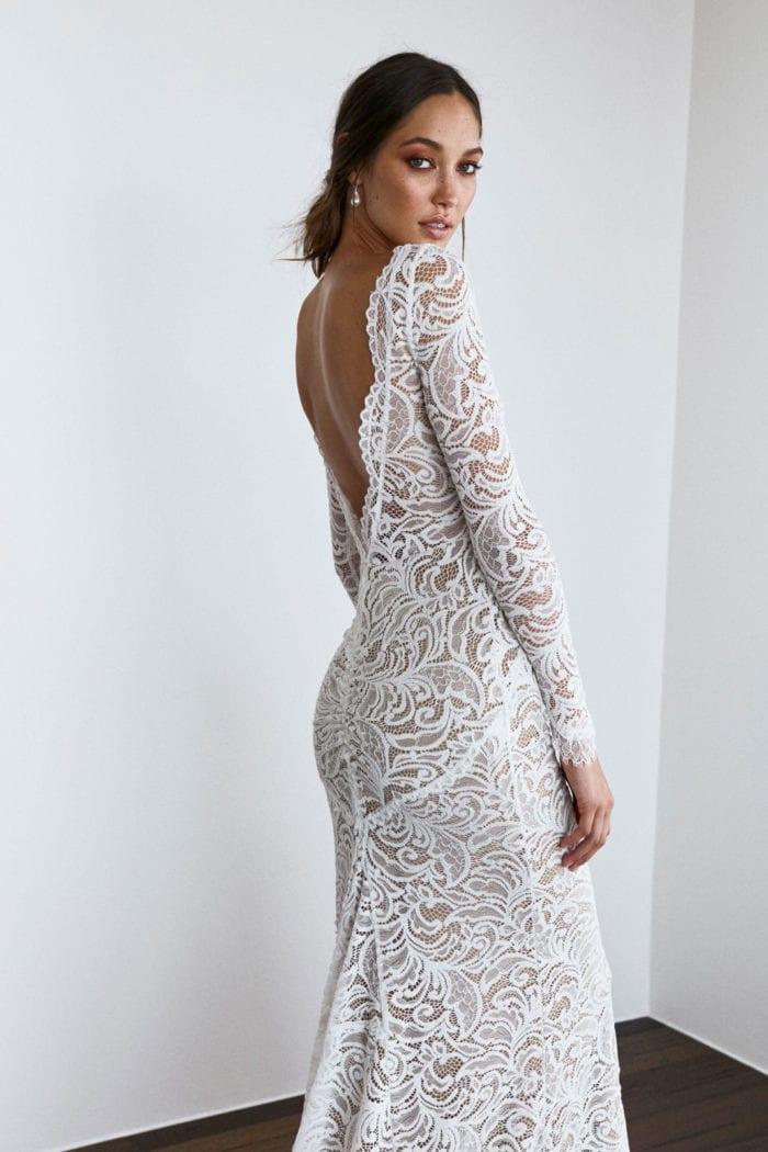 Back shot of bride wearing Grace Loves Lace Orla Gown looking over shoulder