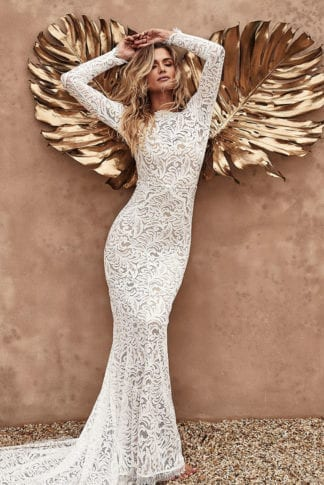 Bride wearing Grace Loves Lace Orla Gown leaning against wall with two gold palm fronds behind