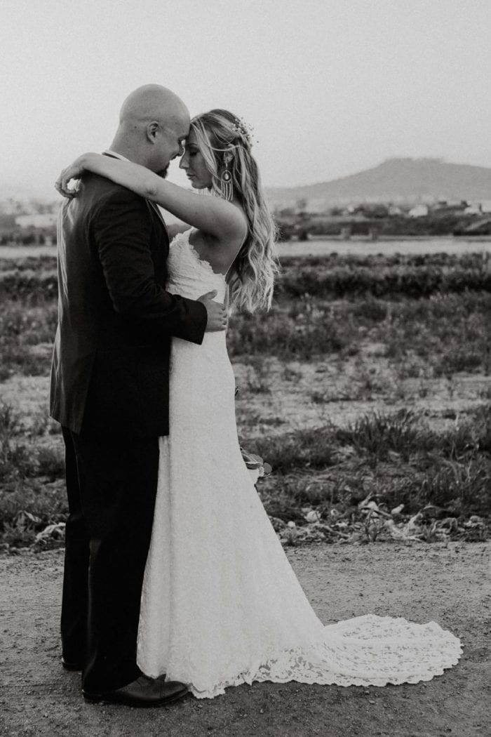 Black and white shot of bride wearing Grace Loves Lace Mia Gown embracing groom
