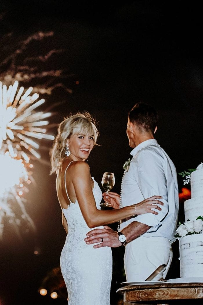 Blonde bride wearing Grace Loves Lace Mia Gown holding champagne glass standing with groom watching fireworks