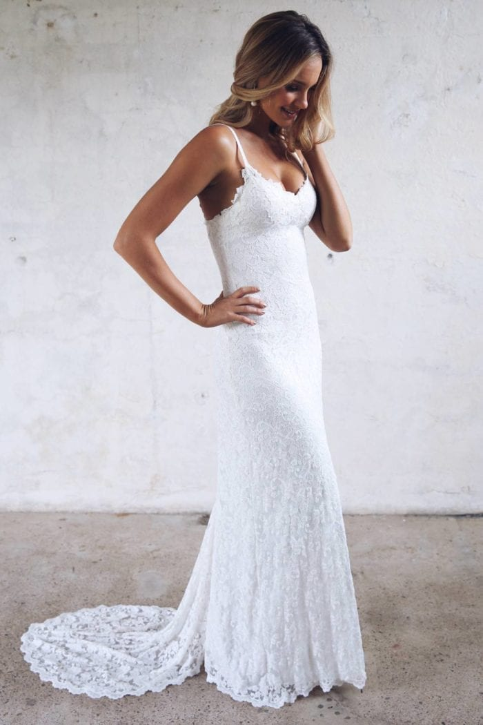 Blonde bride wearing Grace Loves Lace Mia Gown with hand on hair
