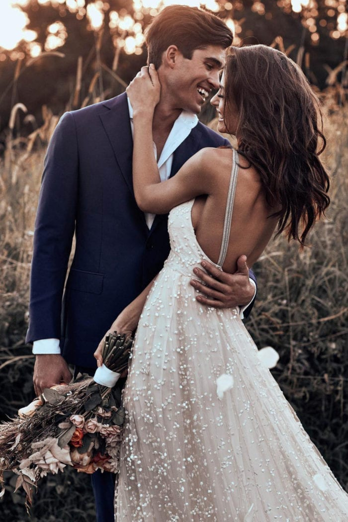 Brunette bride wearing Grace Loves Lace Menha Gown embracing groom
