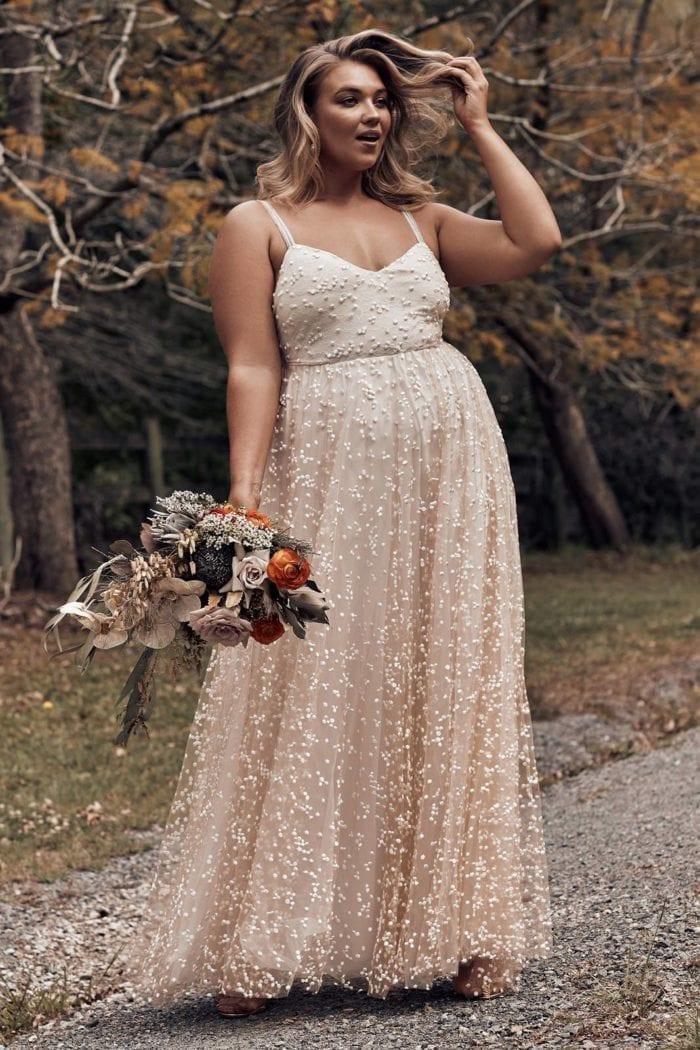 Brunette bride wearing Grace Loves Lace Menha Gown holding bouquet
