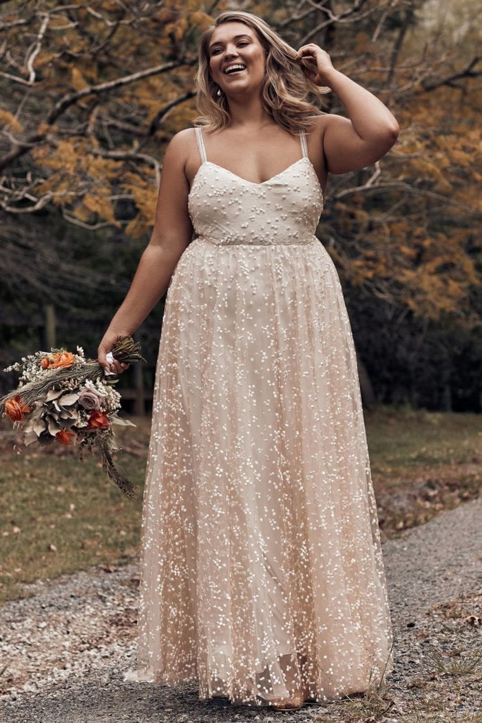 Blonde bride wearing Grace Loves Lace Menha Gown holding bouquet