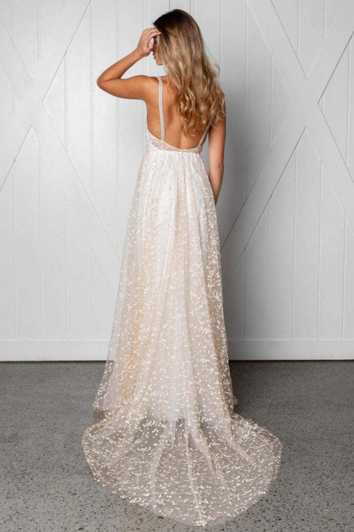 Back shot of blonde bride wearing Grace Loves Lace Menha Gown with hand in hair