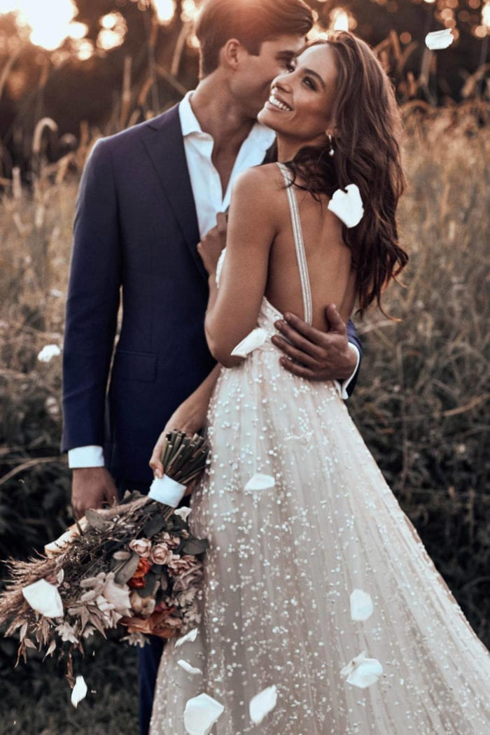 Brunette bride wearing Grace Loves Lace Menha Gown being held by groom