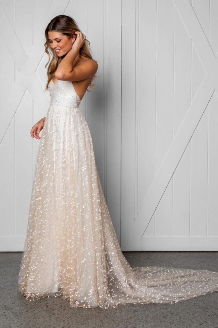 Blonde bride wearing Grace Loves Lace Menha Gown with hand on hair