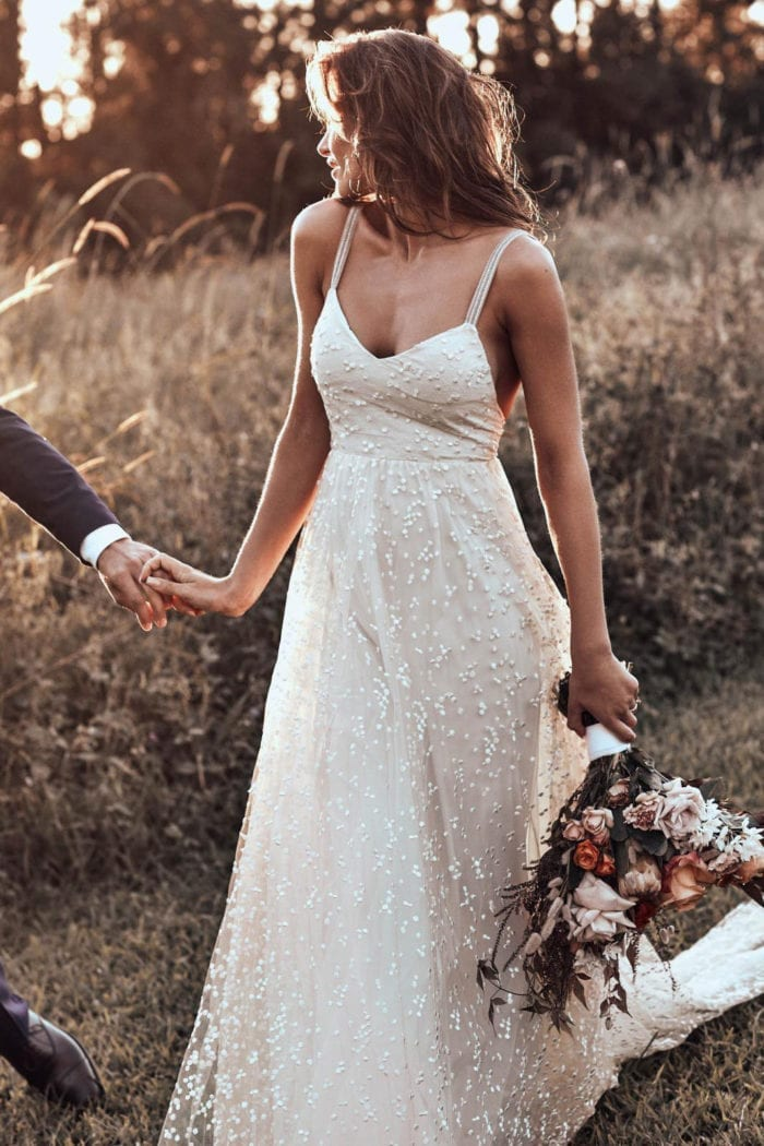 Brunette bride wearing Grace Loves Lace Menha Gown holding bouquet