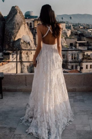 Back shot of bride wearing Grace Loves Lace Megan Gown holding skirt