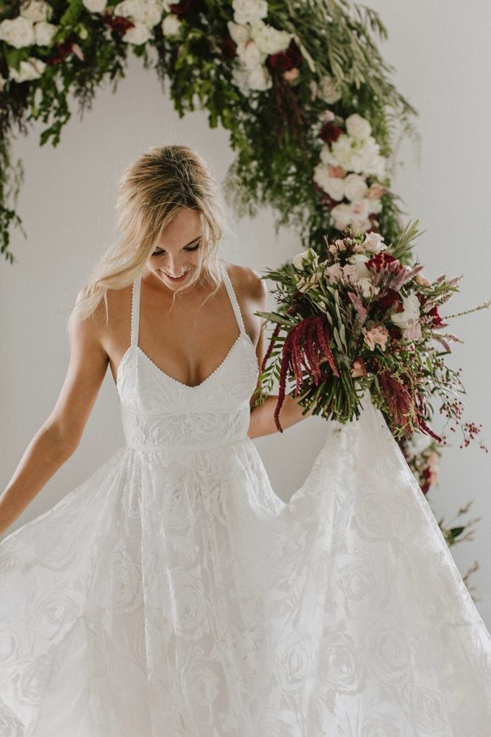 Blonde bride wearing Grace Loves Lace Megan Gown holding bouquet and skirt