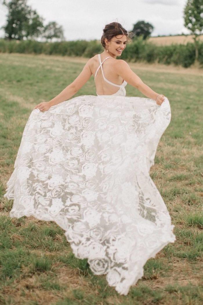 Brunette bride wearing Grace Loves Lace Megan Gown holding skirt in hands in grassy field