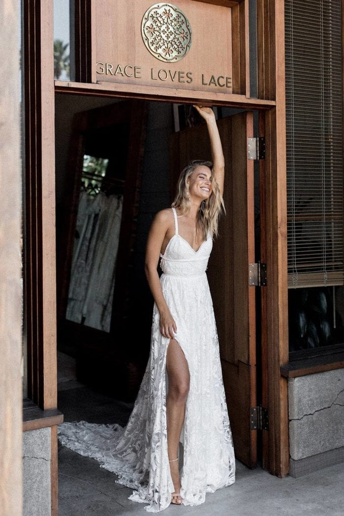 Blonde bride wearing Grace Loves Lace Megan Gown with hand above head in doorway