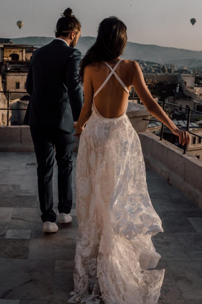 Back shot of bride wearing Grace Loves Lace Megan Gown holding hands with groom