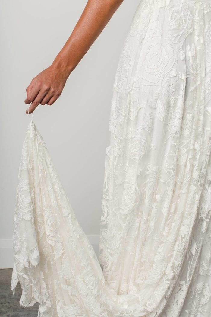 Close-up of bride wearing Grace Loves Lace Megan Gown holding train in finger loop