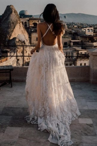 Back shot of bride wearing Grace Loves Lace Megan Gown holding skirt in hands