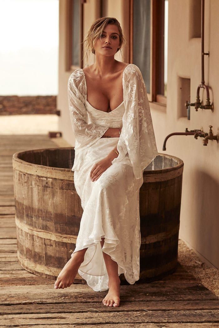 Blonde bride wearing Grace Loves Lace Loyola Gown With Sleeves sitting on large barrel