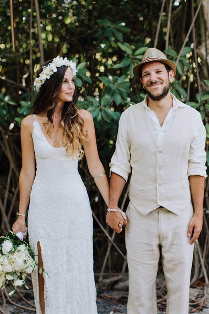 Brunette bride wearing Grace Loves Lace Lottie Gown holding hands with groom