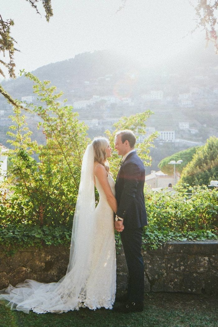 Blonde bride wearing Grace Loves Lace Lottie Gown holding hands with groom