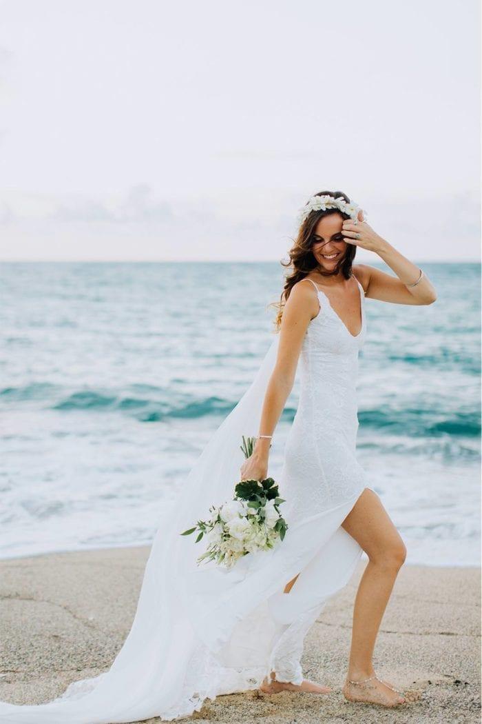Brunette bride wearing Grace Loves Lace Lottie Gown holding bouquet on beach