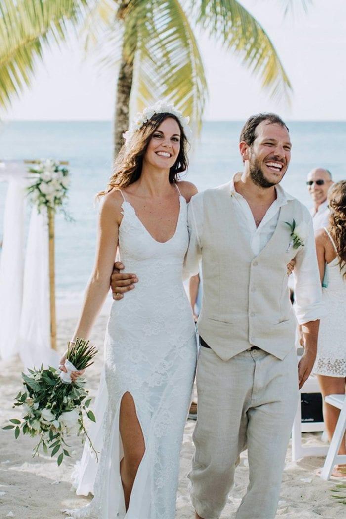 Brunette bride wearing Grace Loves Lace Lottie Gown holding bouquet walking with groom on beach