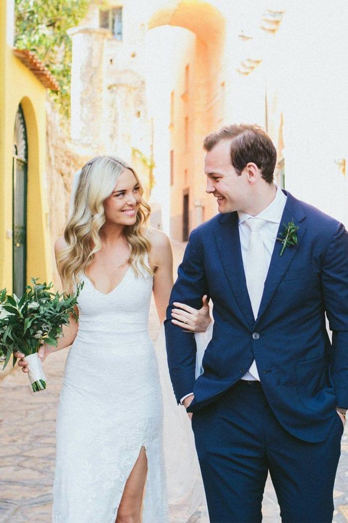 Blonde bride wearing Grace Loves Lace Lottie Gown holding bouquet walking with groom