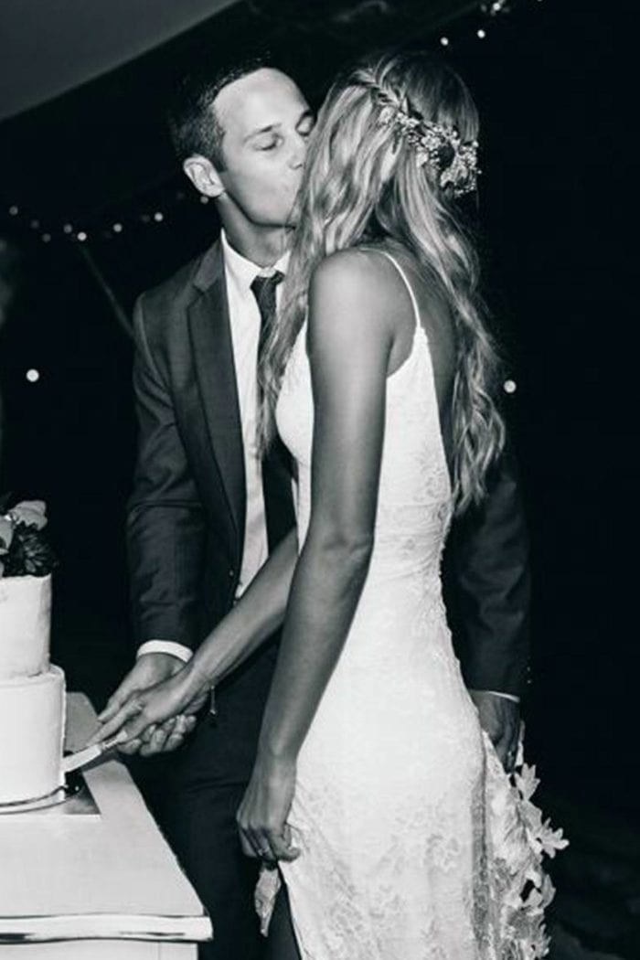 Black and white shot of bride wearing Grace Loves Lace Lottie Gown cutting cake while kissing groom