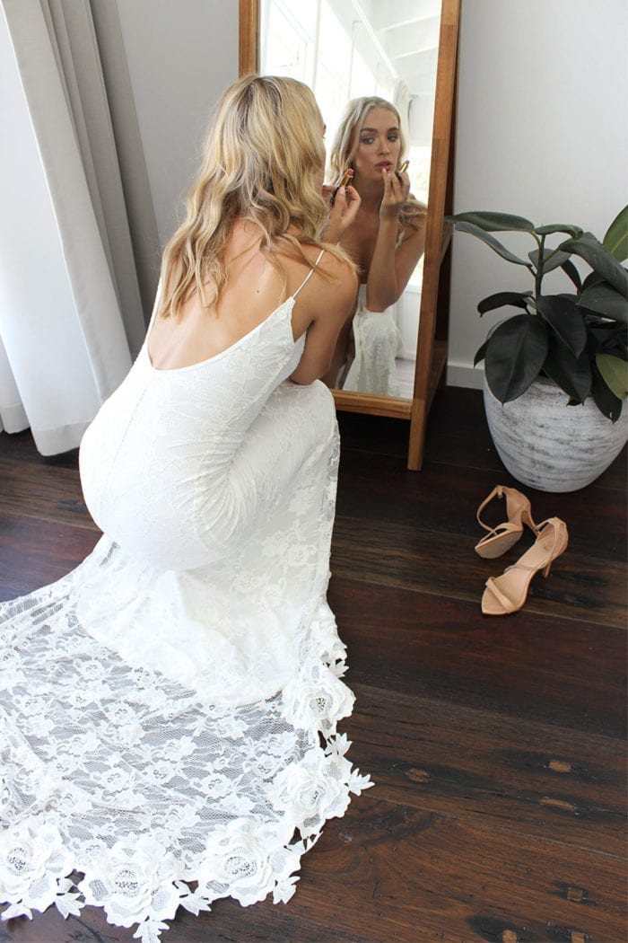 Blonde bride wearing Grace Loves Lace Lottie Gown crouching down in front of mirror putting lipstick on
