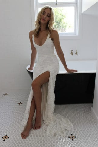 Blonde bride wearing Grace Loves Lace Lottie Gown leaning against bathtub