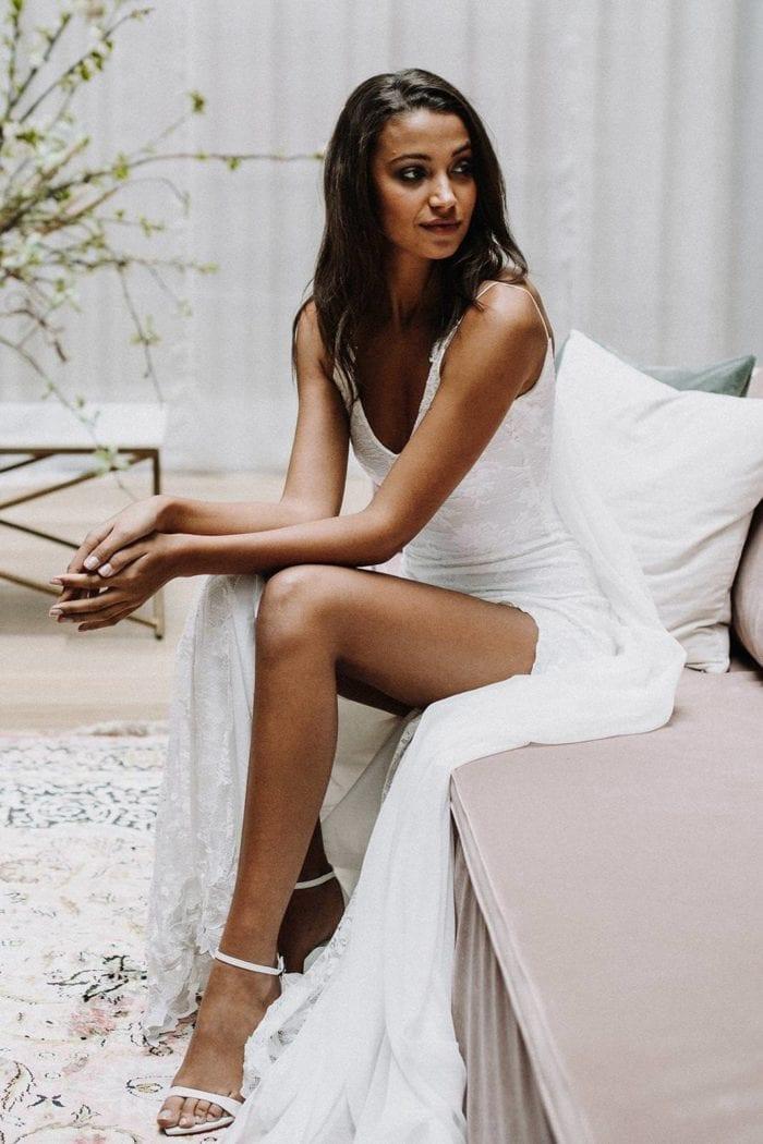 Brunette bride wearing Grace Loves Lace Lottie Gown sitting on sofa