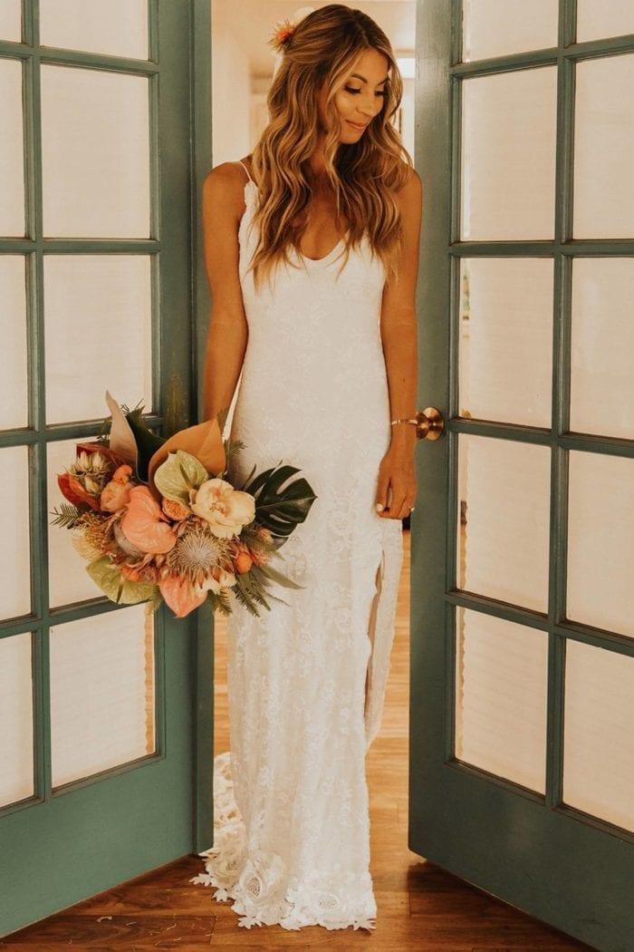 Blonde bride wearing Grace Loves Lace Lottie Gown holding bouquet standing in doorway