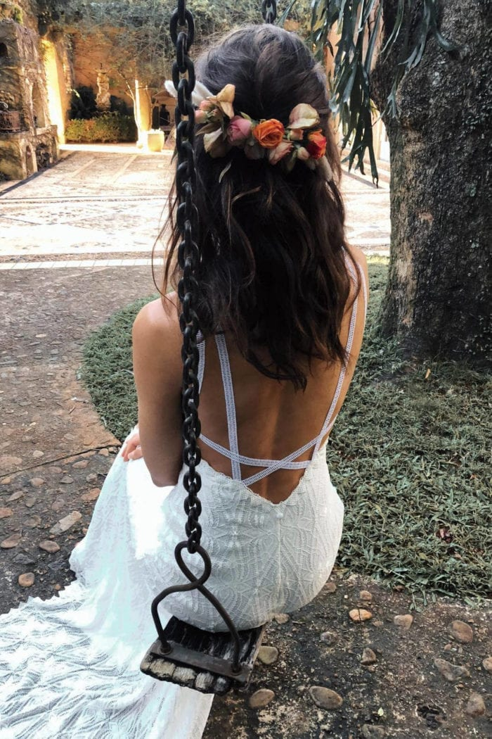 Back shot of bride wearing Grace Loves Lace Leon Gown and flower crown sitting on swing