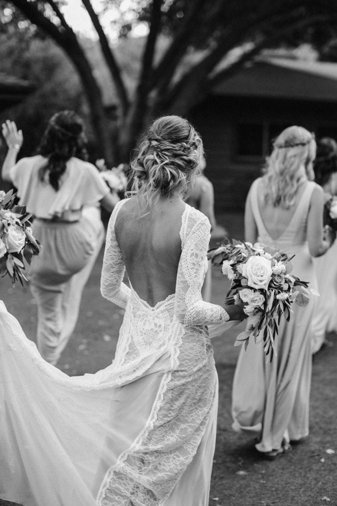 Black and white back shot of bride wearing Grace Loves Lace Inca Gown with bridesmaids
